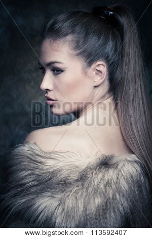 beautiful blue eyes young woman with artificial fur portrait in studio, profile