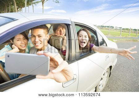 Young  People Enjoying Road Trip In The Car And Making Selfie