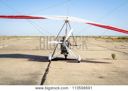 Hang-gliding, standing at dawn on the runway
