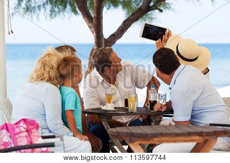 Family selfie with tablet PC in outdoor cafe on resort