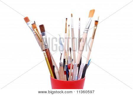 top of red glass with brushes and tools for painting