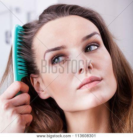 Beautiful young woman combing brown hair