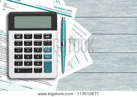 Uk Tax Form With Calculator Lying On Wooden Desk
