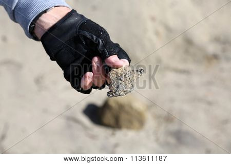 San Clemente CA Jan. 7 2016: A man uses his Metal Detector as he sifts through the sand after the Godzilla El Nino of 2016. Here he shows a piece of scrap metal he found buried in the sand.