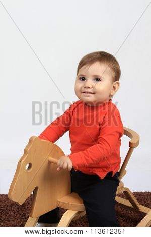 beautiful and happy child on a wood horse