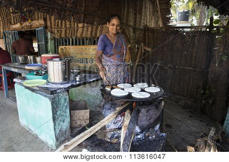Indian woman preparing dosa at a kitchen, Auroville