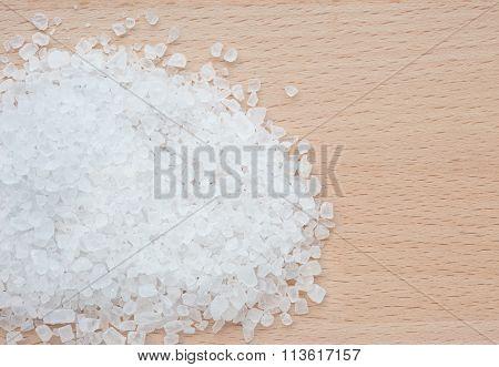 Heap of rock salt on a wooden board