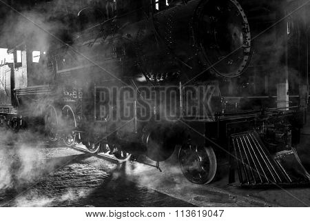Steam locomotive at train station with dramatic lighting and steam