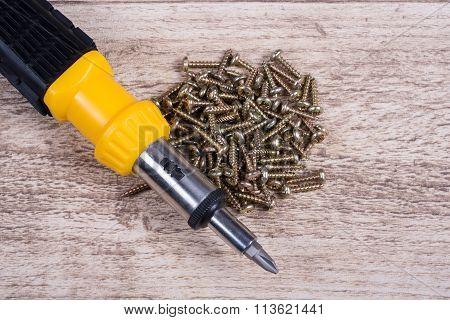 Many Brass Screws And Screwdriver Lying On Wooden Table- Close Up