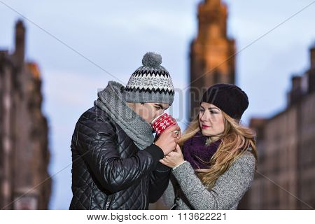 Young Couple In Love Embracing And Drinking Hot Drink From Red Cup