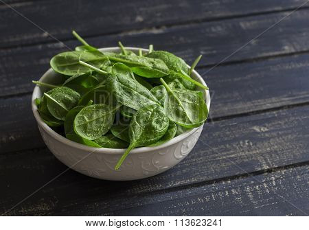Fresh Spinach In A White Bowl On A Dark Wooden Background. Healthy Food