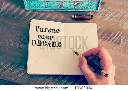 Motivational Message Pursue Your Dreams Written On Notebook