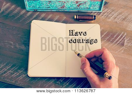 Motivational Message Have Courage Written On Notebook