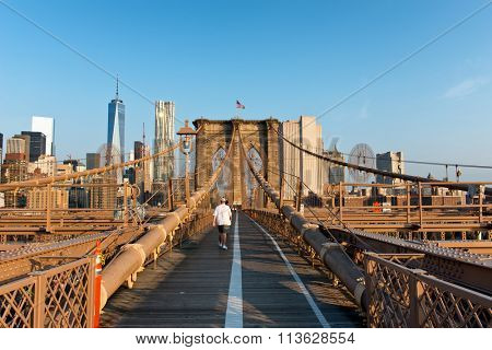 NEW YORK - SEPTEMBER 06: Man walking across Boston Bridge pedestrian walkway towards Manhattan, New York, and the city skyline. September 06, 2015 in New York.