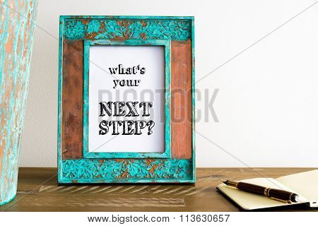 Vintage Photo Frame On Wooden Table With Text What's Your Next Step ?