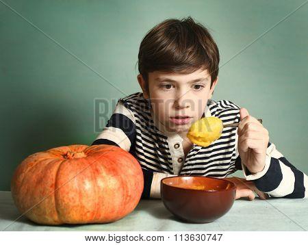 Boy With Big Orange Pumpkin Eat Mash Cream Soup