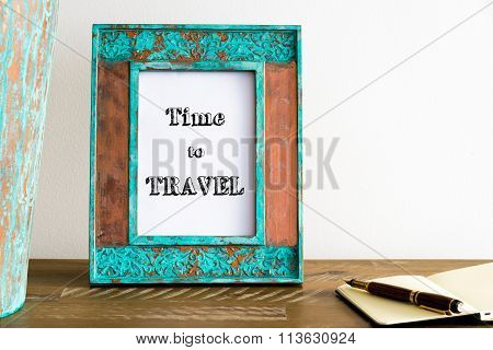 Vintage Photo Frame On Wooden Table With Text Time To Travel