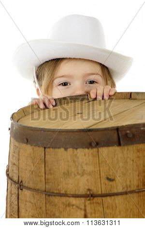 An adorable preschool cowgirl peeking over the top of a rustic old barrel.  On a white background.