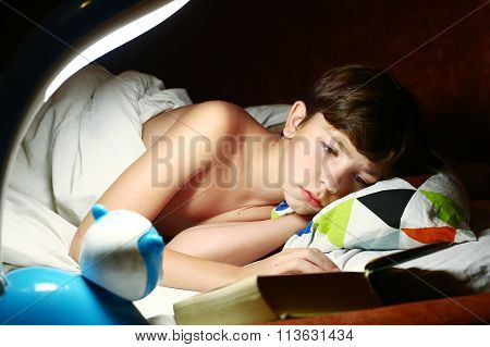 boy  reading book under the blanket in night
