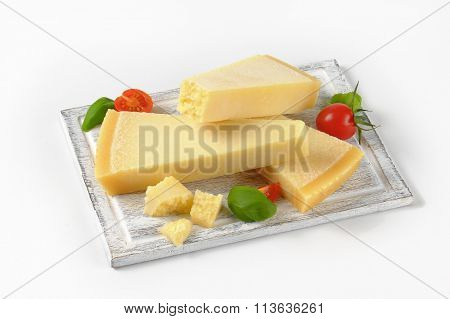 wedges of fresh parmesan cheese on wooden cutting board