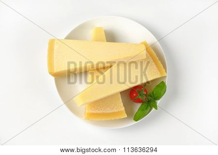 three wedges of fresh parmesan cheese on white plate