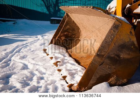Large Excavator Bucket On Ground Covered With Snow