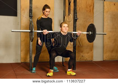 Personal trainer assisting in the squat exercise