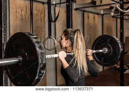 Young female athlete performed squats in the gym
