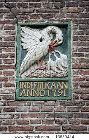 AMSTERDAM, The Netherlands - JULY 9 2014: Decorative gable stone in the wall of an ancient building in Amsterdam. In Middle Ages, these were used to identify the houses as many people couldn't read.