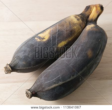 Two Old Banana Fruit On A Wooden Board