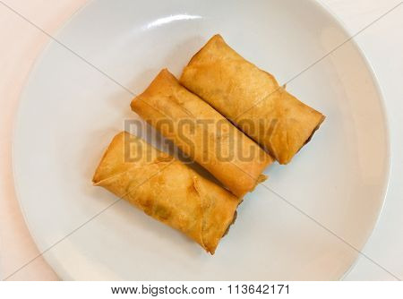 Fried Chinese Spring Rolls In A White Plate