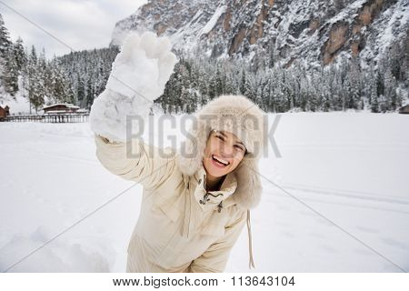 Woman In White Coat And Fur Hat Throwing Snowball Outdoors