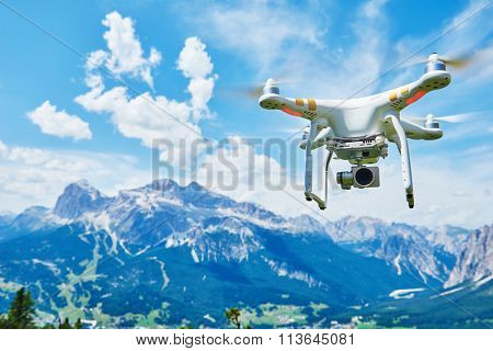 White copter with high resolution digital camera flying in the blue sky over the mountain
