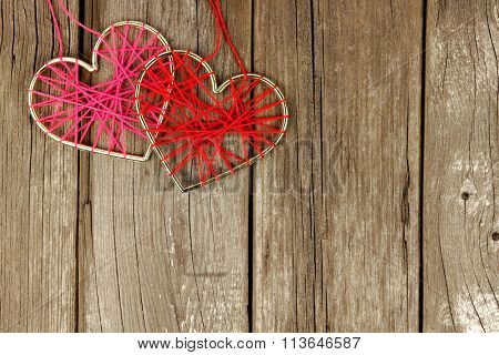 Yarn hearts together on rustic wood