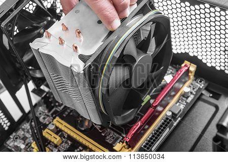 Hands installing a fan on the motherboard.