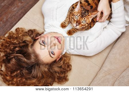 Girl And A Cat Lying On The Couch.