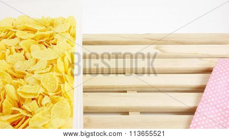Tasty golden corn flakes in plastic container box on wooden tray