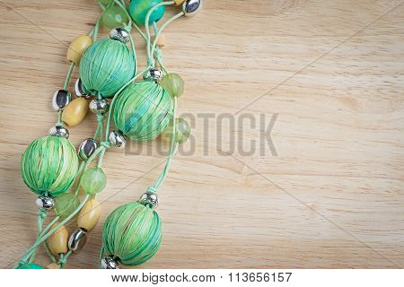 Green Beaded Necklace On Wooden Background Table With Copy Space