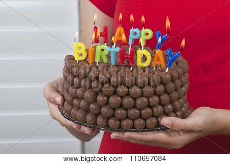 Chocolate cake decorated with rows of malt balls on glass plate held in hands close up