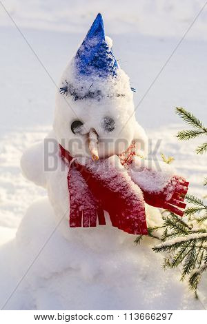 Background winter landscape snowman in a bright blue cap and red scarf in the snow