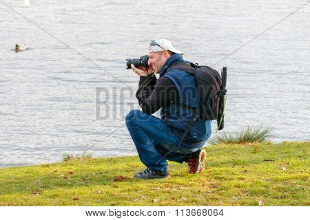 Prague. A man with a camera on the riverbank.