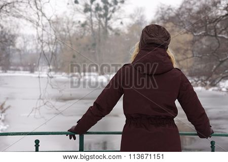 woman looking at frozen river