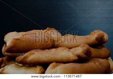 A plate with fresh pies on a black wooden table. Closeup