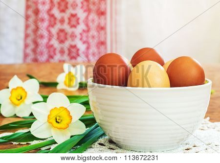 Easter Eggs In A Ceramic Vase And Flowers Daffodils.