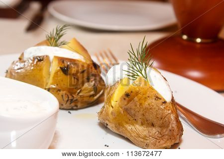 Baked Potato Is On The Plate With Sour Cream And Dill.