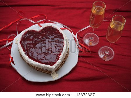 Heart Shaped Cake With Red Marmalade On Vintage Dish And Two Glasses Of Champagne Served On Red Drap
