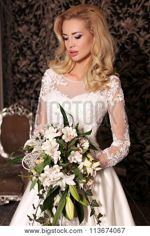 Gorgeous Woman With Blond Hair Wears Luxurious Wedding Dress With Flowers