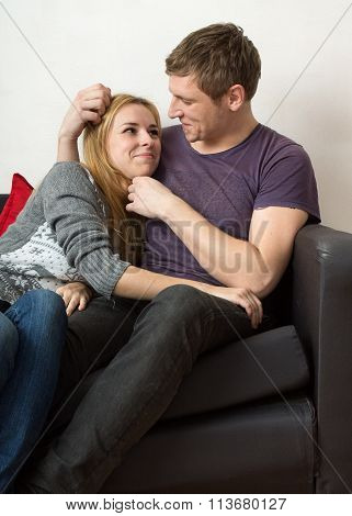 A Couple Is Sitting On The Sofa