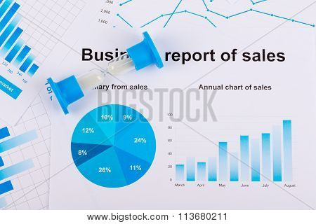 Financial charts and graphs. Sales report on paper. Hourglass. The countdown profits