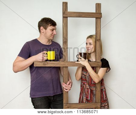 A Couple With Cups Is Resting During The Repair Near A Wooden Construction